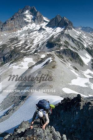 Female climber ascending rock ridge, Redoubt Whatcom Traverse, North Cascades National Park, WA, USA
