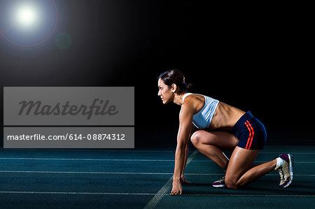 Female athlete in starting position on running track