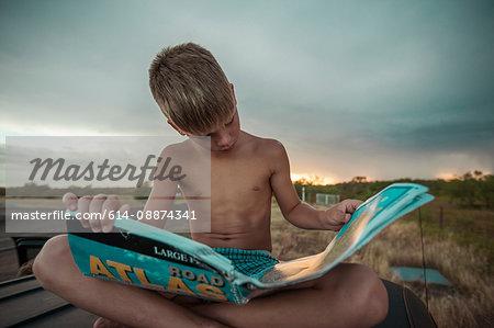 Boy looking at atlas