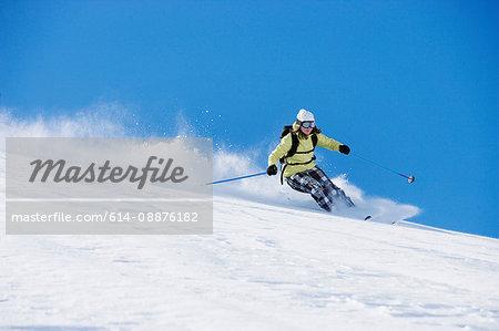 Female skiing down ski run