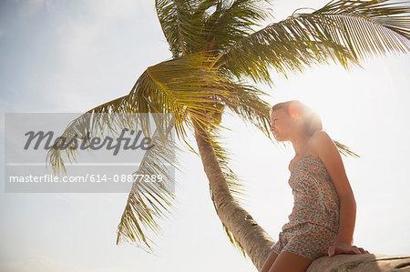 Girl gazing out from palm tree, Rawa Island Malaysia