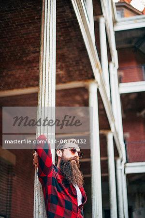 Man with beard leaning against a pillar