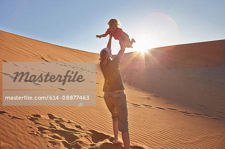 Mother playing with son on sand dune, Namib Naukluft National Park, Namib Desert, Sossusvlei, Dead Vlei, Africa