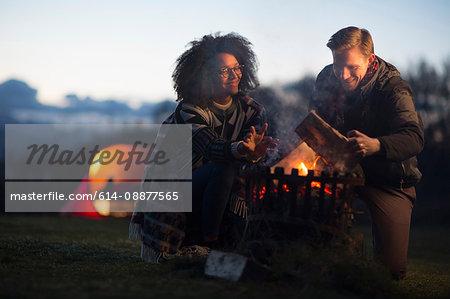 Couple toasting marshmallows at camp, Isle of Skye, Scotland