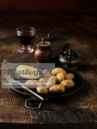 Roasted potatoswith bowl of parmesan fondue on rustic dish