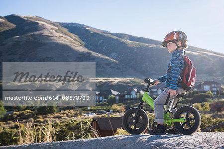 Boy sitting on balance bike in front of mountain, Draper cycle park, Missoula, Montana, USA