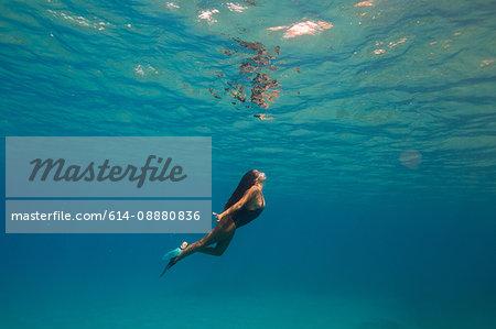 Woman swimming underwater, Oahu, Hawaii, USA