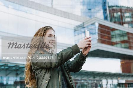 Young woman taking photograph in city, Boston, Massachusetts, USA