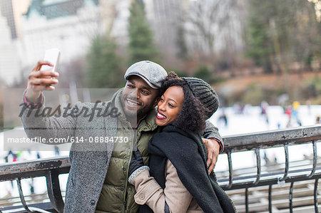Couple taking smartphone selfie on city balcony
