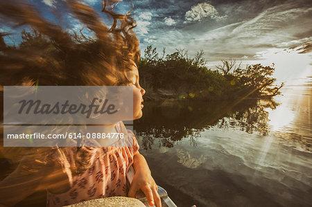 Young girl enjoying cruise on river, eyes closed basking in sunlight, Homosassa, Florida, USA