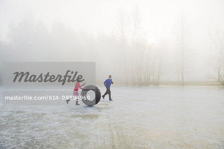 Woman rolling tyre on frozen lake