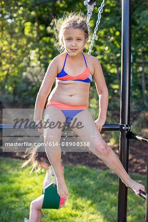 Portrait of girl in bikini sitting on garden climbing frame