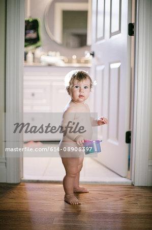Portrait of naked female toddler standing in doorway