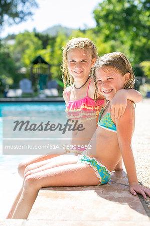 Portrait of two sisters in bikinis sitting on poolside