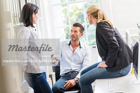 Male designer explaining idea to female colleagues in creative studio meeting
