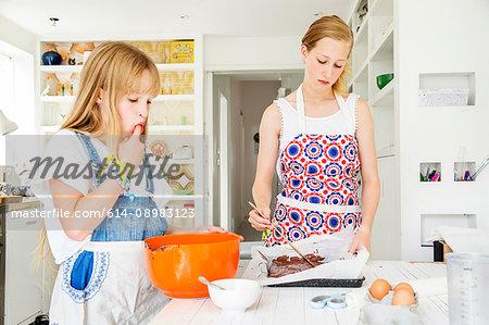 Girls preparing chocolate brownies in kitchen