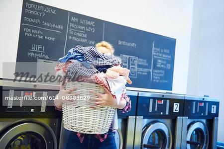Woman in laundrette carrying full laundry basket