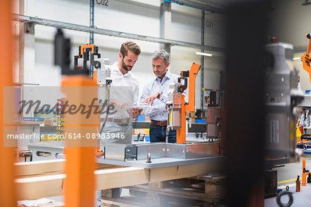Two engineers using digital tablet talking in engineering factory