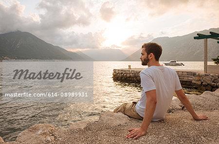 Young man sitting by water looking away, Kotor, Montenegro, Europe