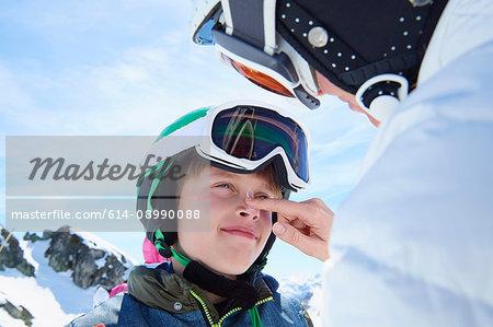 Mother putting sunscreen on son, Hintertux, Tirol, Austria