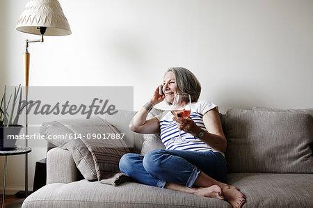 Senior woman with grey bob sitting on sofa making smartphone call
