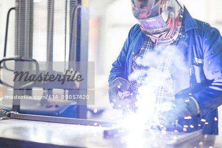 Car mechanic welding in repair garage