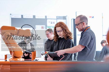 Tutor with robotics apprentices using test industrial robots in robotics facility
