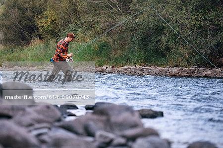 Man wading in river, fishing
