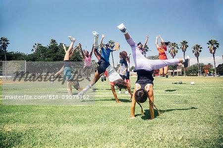 Schoolgirl soccer team doing cartwheel celebration on school sports field