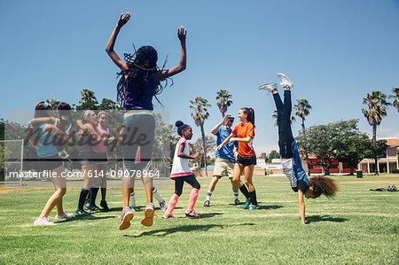 Schoolgirl soccer team jumping for joy on school sports field