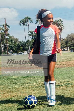 Teenage schoolgirl soccer player on school sports field