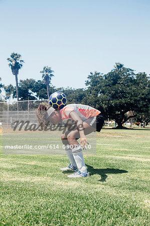 Teenage schoolgirl soccer player balancing ball on shoulders on school sports field