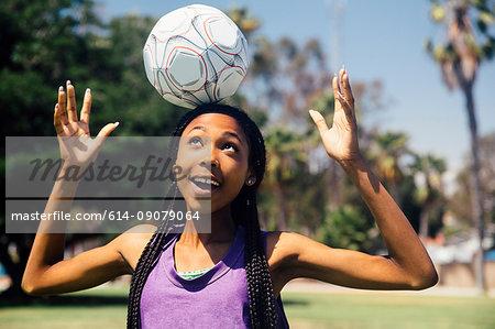 Teenage schoolgirl soccer player balancing ball on head on school sports field