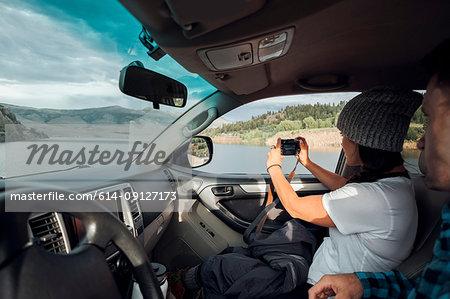 Couple in car, young woman taking photograph through car window, Silverthorne, Colorado, USA