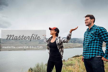 Couple walking near Dillon Reservoir, young woman's arms raised, Silverthorne, Colorado, USA