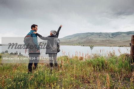 Couple hiking, standing beside Dillon Reservoir,  Silverthorne, Colorado, USA