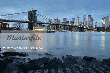 Cityscape with Brooklyn Bridge and Lower Manhattan skyline at dusk, New York, USA