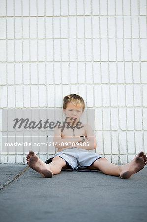 Boy with dirty feet sitting by brick wall