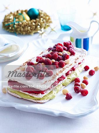 Tray of raspberry macadamia vacherin layer cake on decorated table