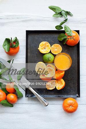 Still life of fresh orange fruits and fruit juice on tray