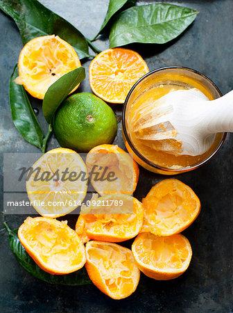 Still life of freshly squeezed orange fruits and juicer