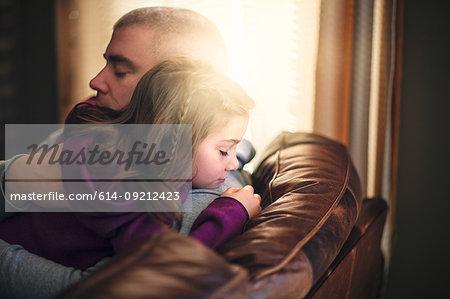 Mature man relaxing on sofa hugging daughter