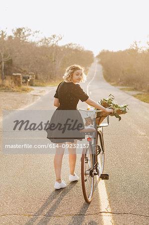 Young woman pushing bicycle on rural road, rear view portrait, Menemsha, Martha's Vineyard, Massachusetts, USA