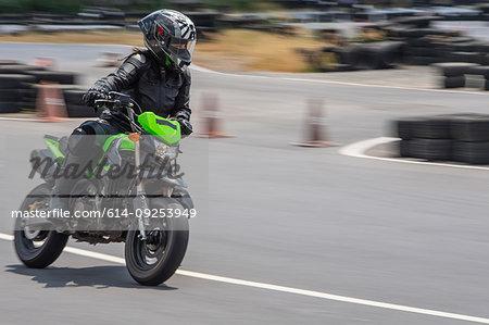 Female motorcyclist speeding on motorbike on race track,  Bangkok