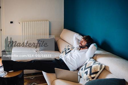 Mid adult man reclining on sofa listening to headphones
