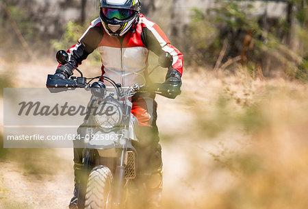 Man riding on his scrambler type enduro motorbike on dirt track, rear view, Bangkok, Thailand