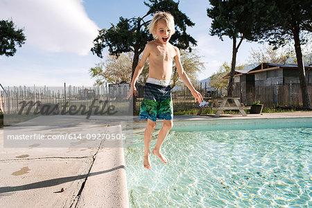 Boy jumping into swimming pool, Olancha, California, US