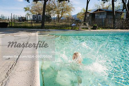 Boy splashing in swimming pool, Olancha, California, US
