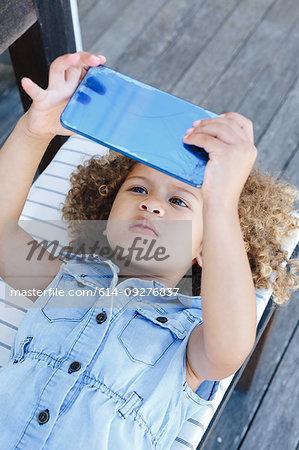 Little girl using smartphone on bench