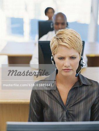 Businesspeople using computer, wearing headphones